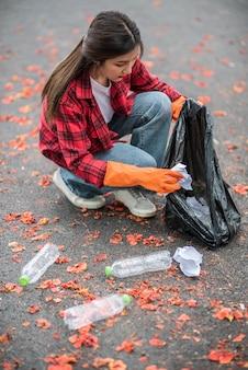 Mujer recogiendo basura en una bolsa negra.