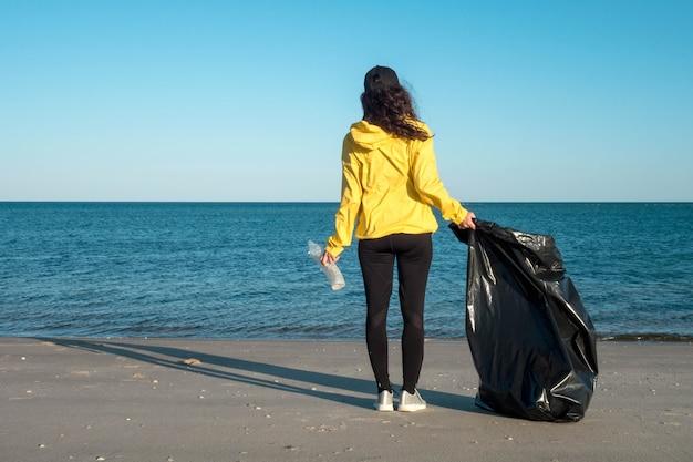 Mujer recogiendo basura y plásticos limpiando la playa con una bolsa de basura. activista voluntario ambiental contra el cambio climático y la contaminación de los océanos.