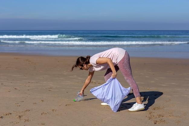 Mujer recogiendo basura y plásticos limpiando la playa