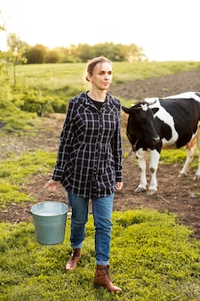 Mujer recogiendo leche de vaca