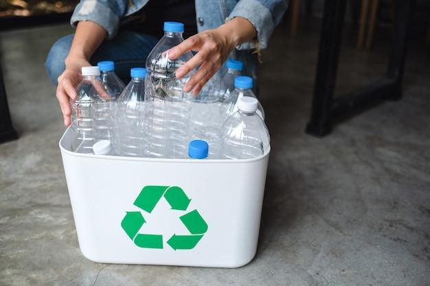 Una mujer recogiendo y separando botellas de plástico de basura reciclable en un contenedor de basura en casa