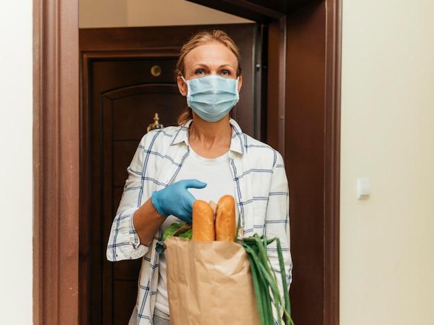 Mujer recogiendo sus comestibles en autoaislamiento en casa