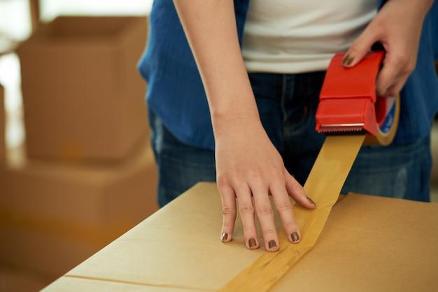 Mujer recortada irreconocible que empaca una caja con dispensador de cinta adhesiva