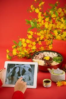 La mujer recortada irreconocible sentada a la mesa servía tradicionalmente mirando fotos antiguas en la pestaña digital contra el fondo rojo.