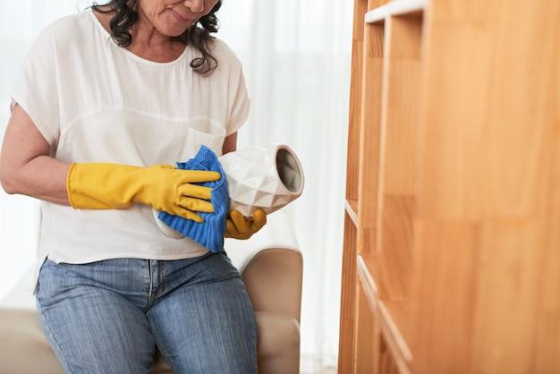 Mujer recortada que limpia el florero con un paño