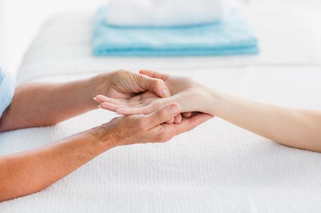 Mujer recortada que recibe masaje de manos