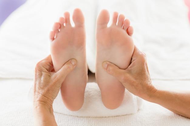 Mujer recortada que recibe masaje de pies