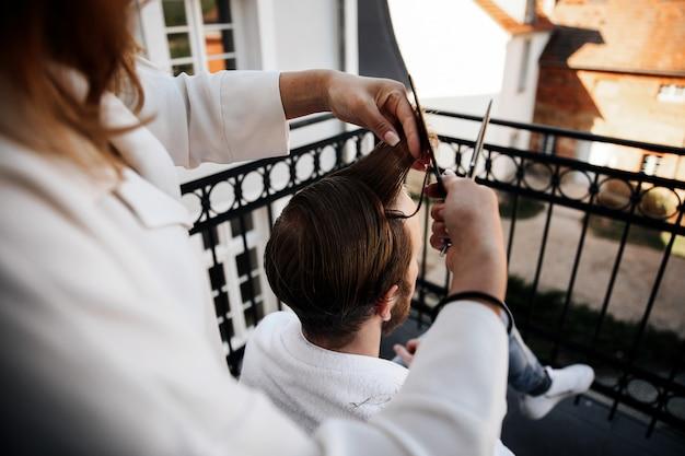 La mujer está recortando el cabello del hombre.