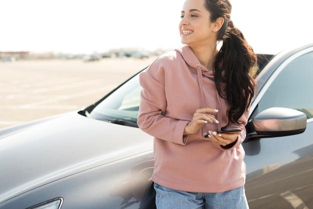 Mujer recostada en el auto al aire libre