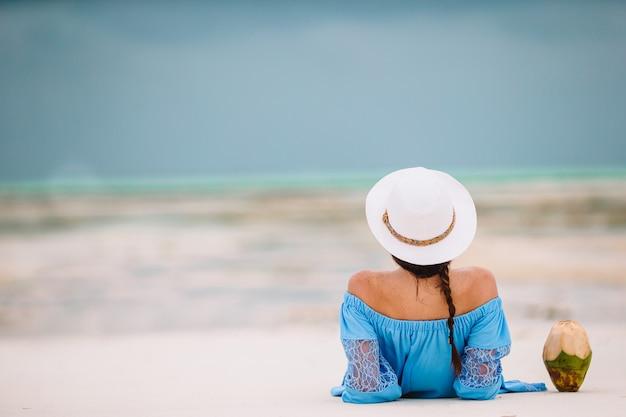 Mujer recostada en la playa disfrutando de las vacaciones de verano mirando al mar