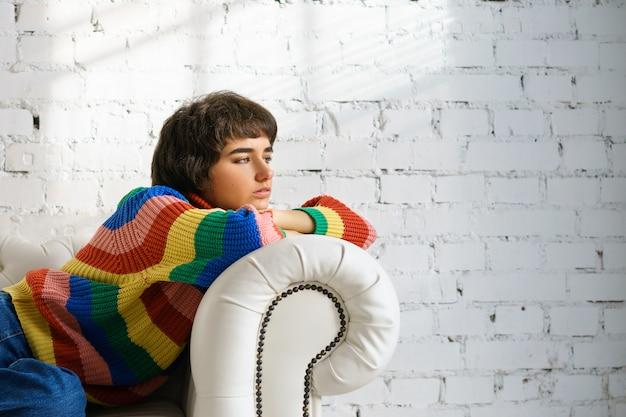 Mujer está recostada en un sofá con un suéter multicolor y calcetines