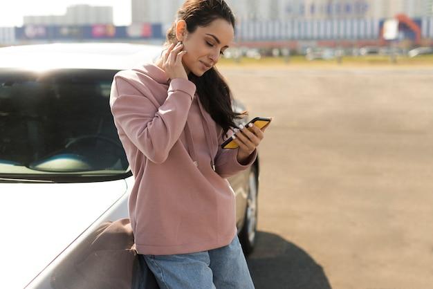 Mujer recostada en su vehículo