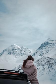 Mujer recostada en un vehículo negro frente a increíbles montañas nevadas y rocosas y cielos nublados