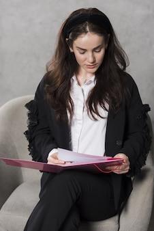 Mujer de recursos humanos sosteniendo y leyendo el currículum