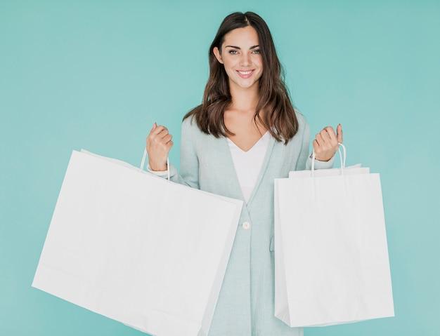 Mujer con redes de compras sobre fondo azul.