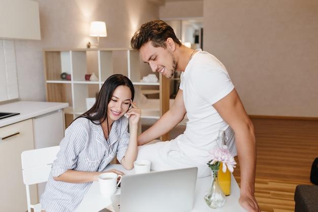 Mujer refinada con cabello negro brillante usando laptop durante el desayuno con novio