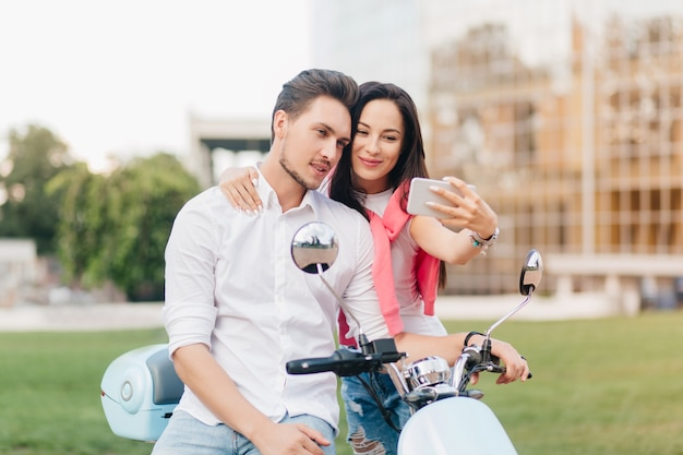 Mujer refinada con cabello negro y linda sonrisa haciendo selfie con novio en cita en fin de semana de verano