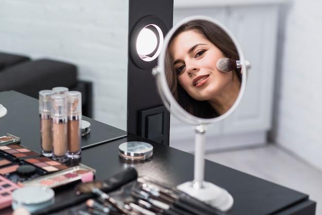 Mujer reflejando espejo y aplicando maquillaje con brocha.