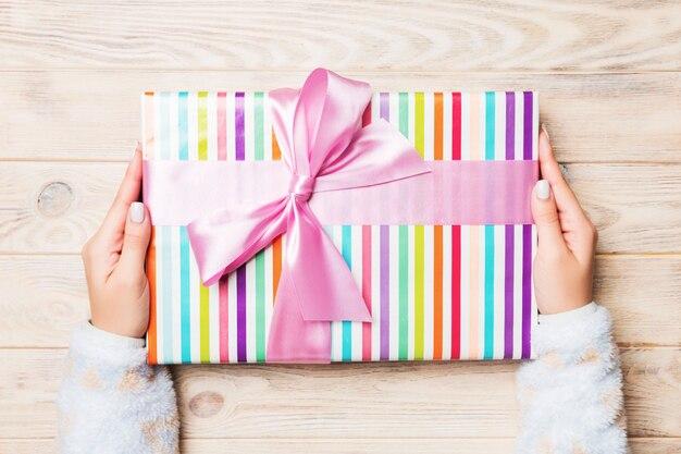 Mujer regala caja de regalo de san valentín con lazo rosa