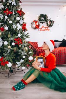 Mujer con regalos por arbol de navidad.