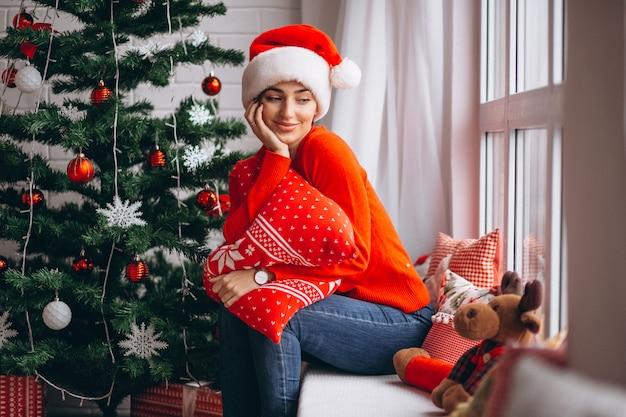 Mujer con regalos de navidad por arbol de navidad