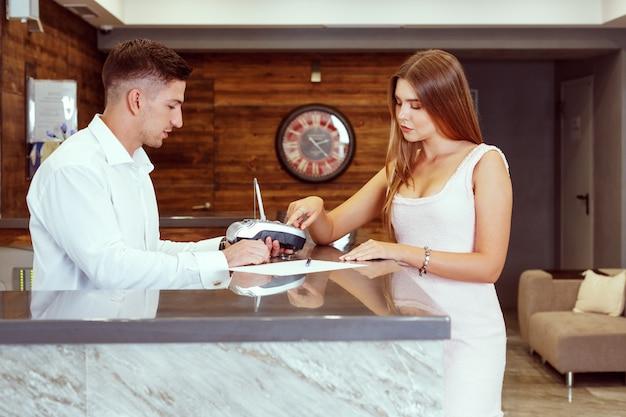 Mujer registrarse en la recepción del hotel