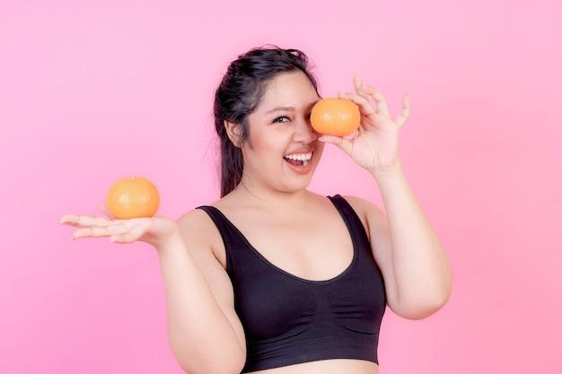Mujer regordeta asiática con sobrepeso con naranja
