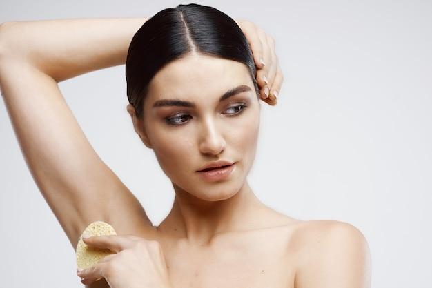 Mujer con rejuvenecimiento de crema para el cuidado de la piel de hombros desnudos