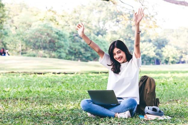 La mujer se relaja con el ordenador portátil que se sienta en hierba en parque