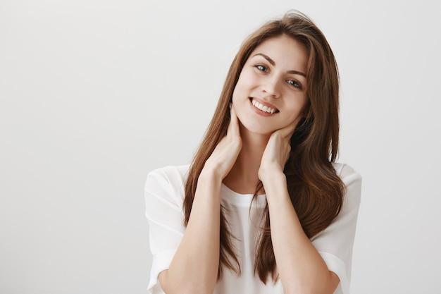 Mujer relajada complacida tocando el cuello y sonriendo, se deshizo del dolor