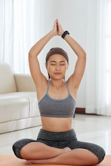 Mujer relajada meditando en casa