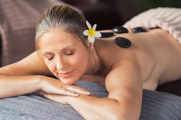 Mujer relajada con piedras calientes en la espalda