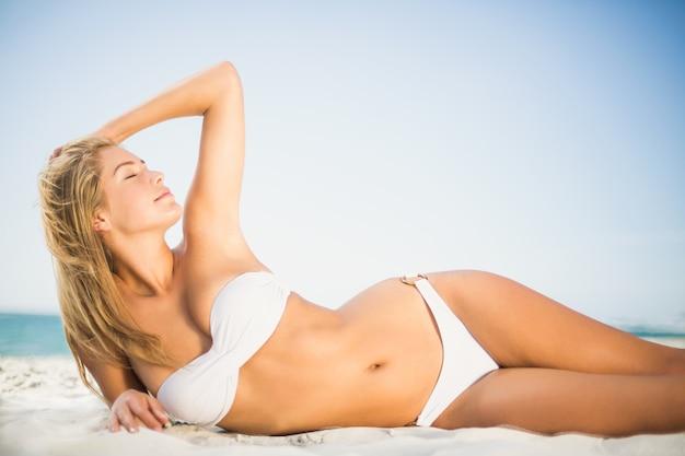 Mujer relajada posando en la playa