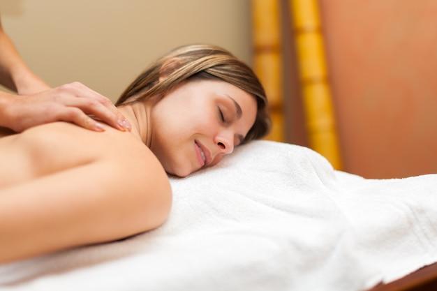 Mujer relajada recibiendo un masaje en un spa