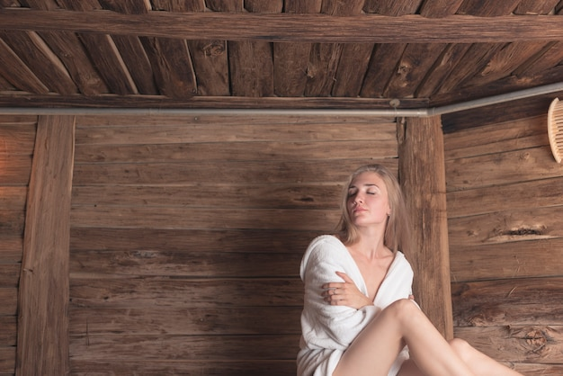 Mujer relajada en sauna abrazándose a sí misma