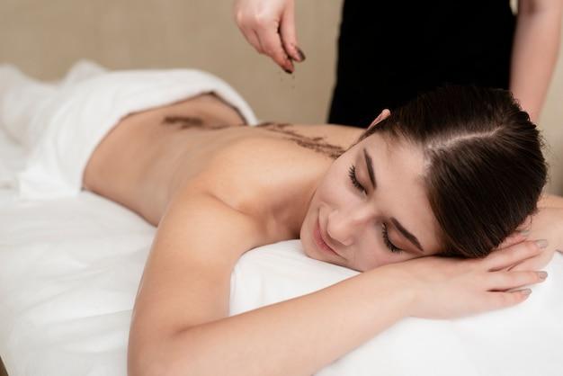 Mujer relajada en el spa recibiendo terapia