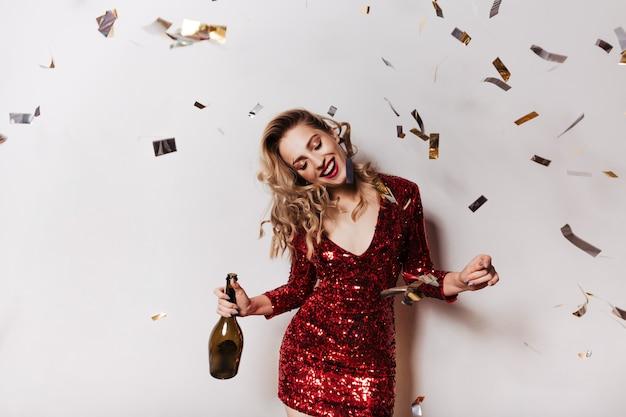 Mujer relajada en vestido rojo brillante celebrando un cumpleaños