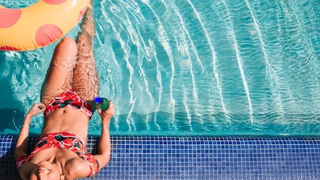 Mujer relajando al lado de piscina