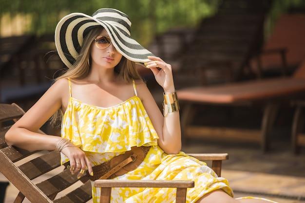 Mujer relajante al aire libre en la tumbona. dama del sombrero. joven mujer en verano. mujer con vestido amarillo.