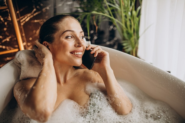 Mujer relajante en el baño con burbujas y hablando por teléfono