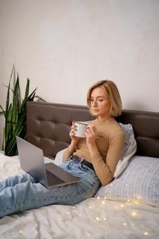 Mujer relajante y bebiendo una taza de té o café caliente usando la computadora portátil en el dormitorio.