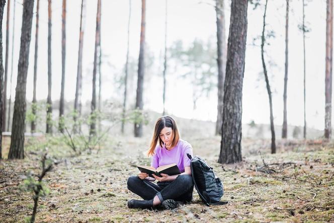 Mujer relajante con libro en el bosque
