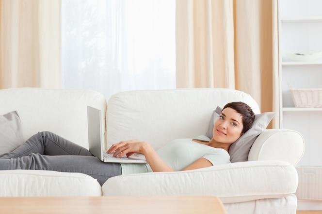 Mujer relajante con una computadora portátil
