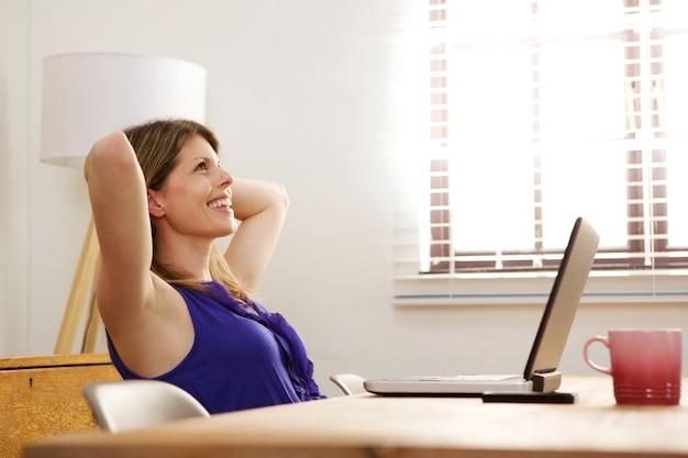 Mujer relajante en el trabajo con la computadora portátil