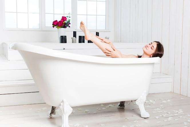 Mujer relajante en la bañera en el baño elegante