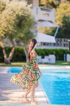 Mujer relajante junto a la piscina en un hotel de lujo