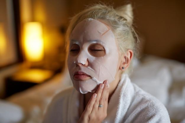 Mujer relajante en máscara facial