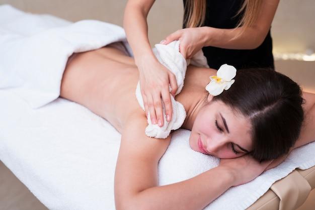 Mujer relajante mientras recibe tratamiento de spa
