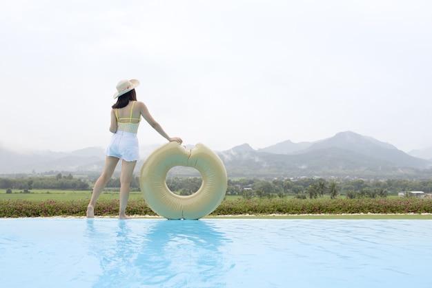 Mujer relajante en la piscina de borde infinito mirando a la montaña