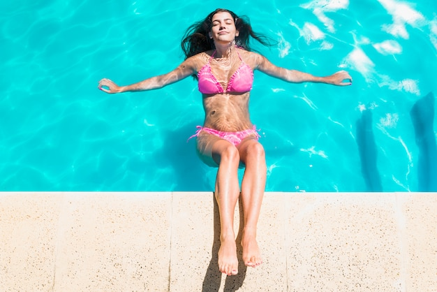 Mujer relajante en piscina con los ojos cerrados